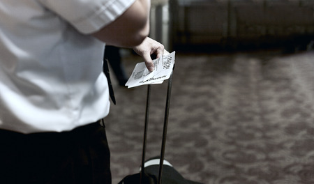 attire: Man dressed in business attire holding flight deck boarding passes Stock Photo