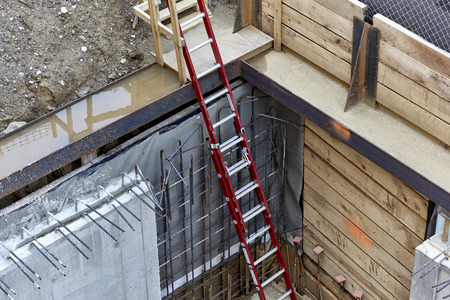 buildingsite: Cement basement foundation walls with rebar and steel reinforcements with ladder