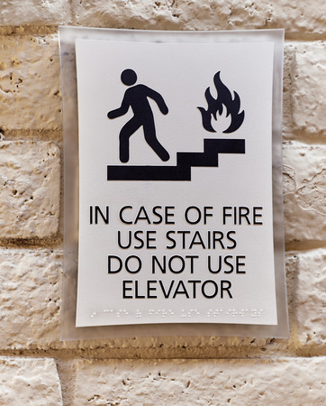 braille: In Case of Fire Use Stairs Do not use Elevator warning sign Stock Photo