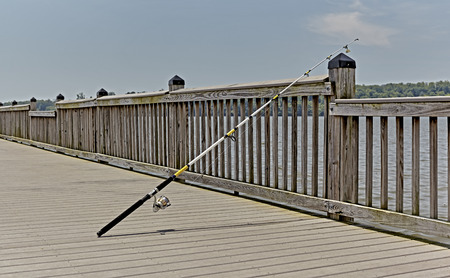fishing rig: Fishing pole on pier resting on guard rail Stock Photo