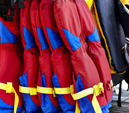 emergency vest: Stack of red boating life jackets hanging on rack on pier