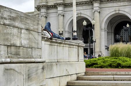 pauper: Washington DC, USA - June 5, 2016: Homeless man sleeping on a marble wall at Union Station Washington DC Editorial