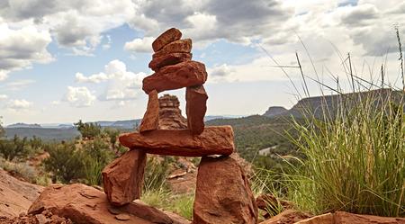 balanced rocks: Stacked red rocks balanced on side of mountain