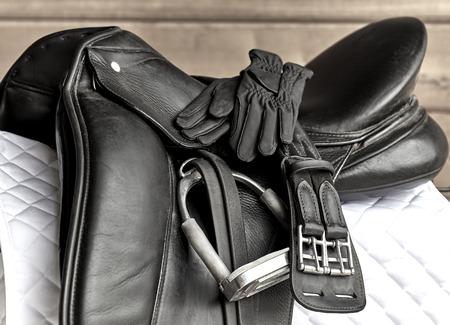 stirrup: Used black dressage horse riding saddle with girth, stirrup and riding gloves on white saddle pad