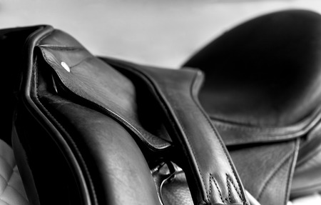 cantle: Used black dressage horse riding saddle with  white saddle pad, girth and shallow depth of field Stock Photo