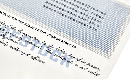 brokerage: Close up of a stock cerficate representing shares in a company with an American one hundred dollar bills