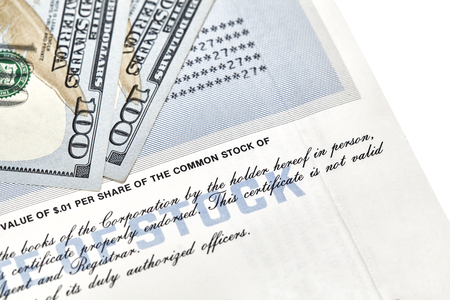 stock certificate: Close up of a stock cerficate representing shares in a company with an American one hundred dollar bills