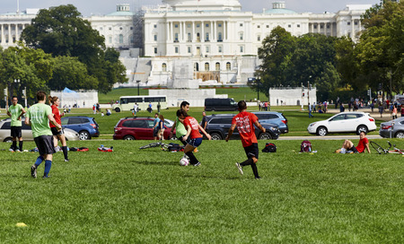 congressional: Washington DC, USA - October 1, 2016 Soccer players on the grass in the park in front of US Capital Building Editorial