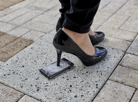stepping: Black patent leather spiked heel womans shoe stepping on a cell phone