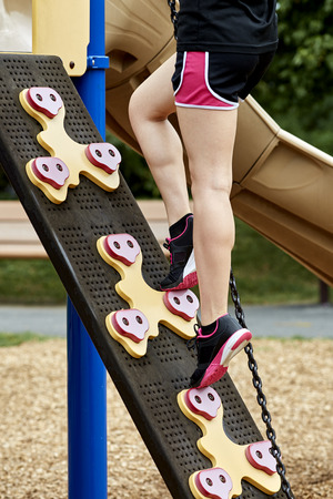 stepping on: Legs of a young girl climing up stepping blocks on playground equipment