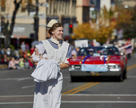 cruz roja: Prescott, Arizona, USA - November 11, 2016: Woman dressed as a Red Cross nurse with infant marching in Veterans Day Parade