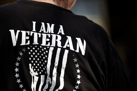 armed services: Back of a mans black t shirt saying I am a Veteran with teh American flag