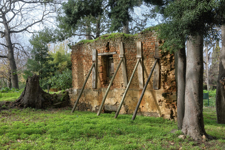 crumbling: Crumbling brick wall propped up with wooden stays