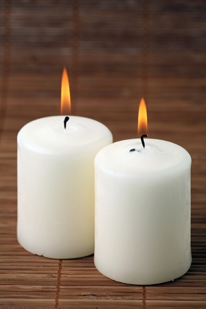 Two burning candles on a bamboo napkin photo