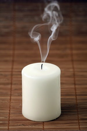 One gone out candle on a bamboo napkin  photo