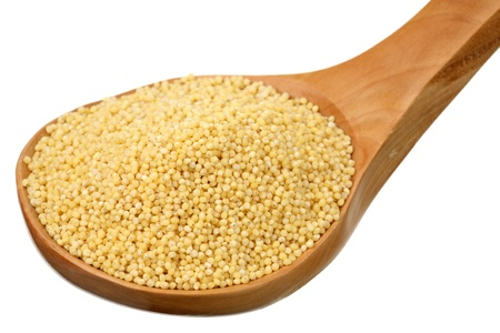 Millet in a wooden spoon on a white background