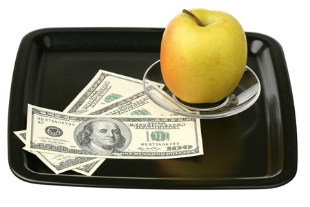 US dollars and yellow apple on a tray  photo