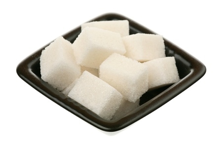 White sugar filled in a small square saucer