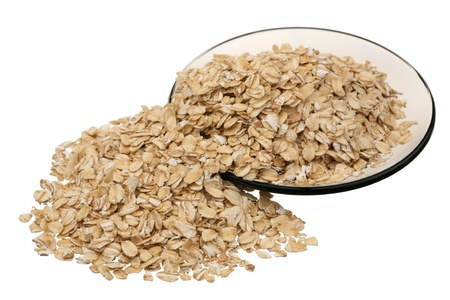 Rolled oats on a glass saucer on a white background  Stock Photo