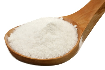 Salt in a wooden spoon on a white background