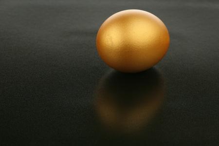 reflexion: Huevo de oro y su reflexi�n sobre un fondo oscuro  Foto de archivo