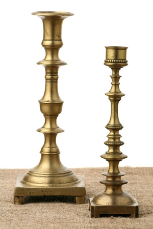 Two old brass candlesticks against a sacking