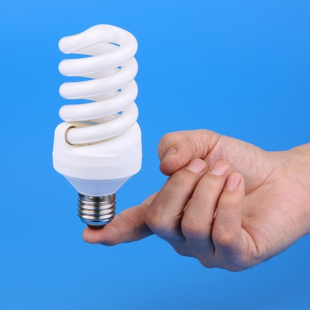 allocated: Luminescent bulb and mans hand on a blue background  Stock Photo