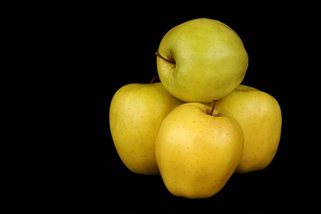 Four yellow apples on a black background