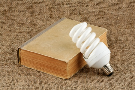 The power saving up bulb and the book lie on a sacking  Stock Photo