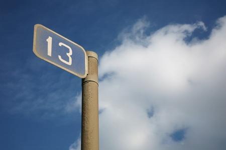 chilometro: Il tredicesimo chilometro - un segno guida contro il cielo nuvoloso Archivio Fotografico