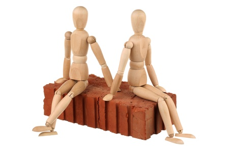Two dummy sitting on a red brick isolated on white background photo