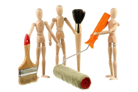 The wooden dummy holding painting brush and roller isolated on white background photo