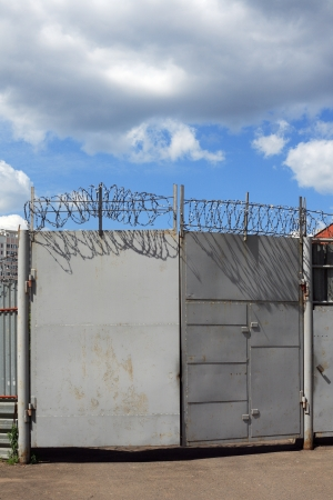 Gates with barbed wire and cloudy sky Stock Photo - 13905864