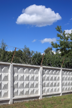 White clouds on blue sky behind barbed wire photo