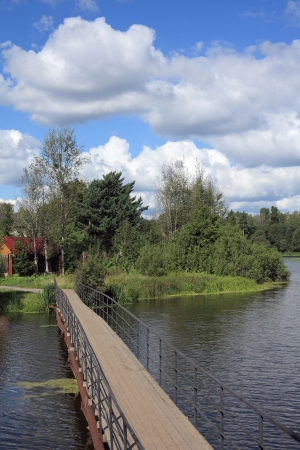 A pedestrian bridge across the river and the beautiful cloudy sky Stock Photo - 14884968