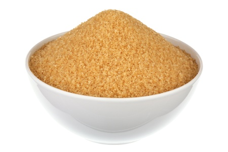 Brown sugar in a plate over white background photo
