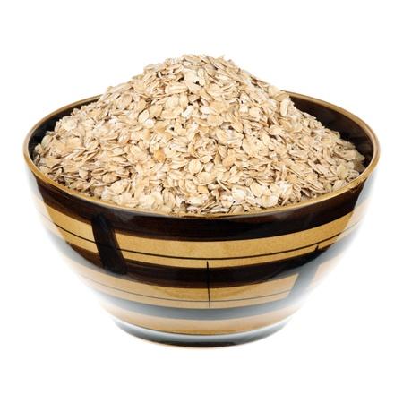 avena en hojuelas: Copos de avena en un plato de cer�mica sobre fondo blanco