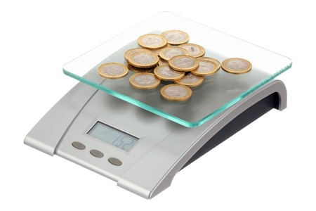 Coins on electronic scales isolated over white background