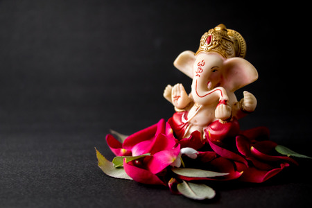 Lord Ganesha Idol with rose petals, white flowers and leaves on Black background, Ganesh pooja
