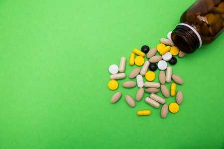 A close up of a bunch of pills coming out of a dark brown bottle with a green space  background.