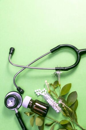 Homeopathic substance in white and brown bottle surrounded with Stethoscope and leaf on green background