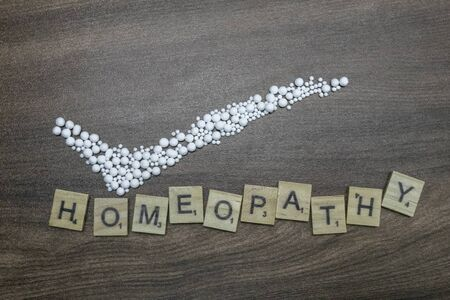 A homeopathy concept. Right mark with homeopathic pills and Homeopathy text on wood background Stockfoto