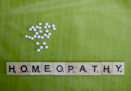 Scattered Homeopathic globules on banana leaf with Homeopathy text
