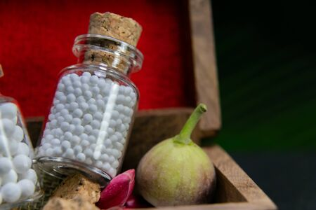Classic Homeopathy concept - Close up of homeopathic pills bottles with wild flower bud, wild fruit in wooden old box on dark background