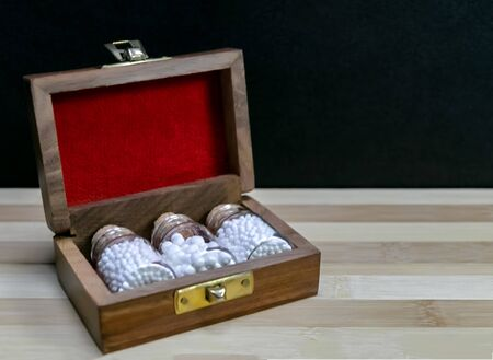 Glass Bottles of homeopathic pills in old opened wooden box on dark background - classic Homeopathy concept