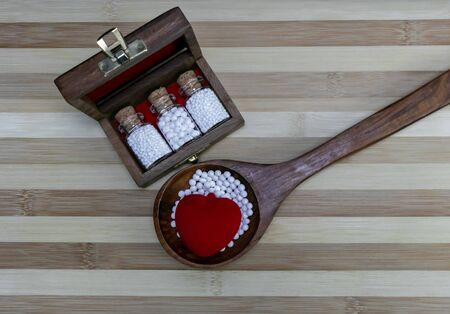 Homeopathic medicine for healthy heart - Glass Bottles of homeopathic medicine in a wooden box with scattered pills and heart in wooden spoon on wood background Standard-Bild