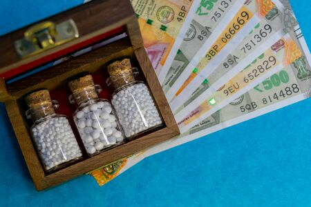 Top view image of wooden box with homeopathic globules bottles and money on blue background. Affordable Homeopathy concept Foto de archivo