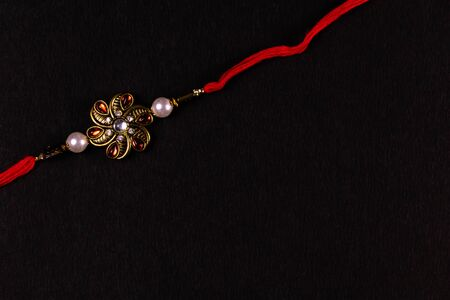 Elegant rakhi isolated black background. A traditional Indian wrist band which is a symbol of love between Brothers and Sisters