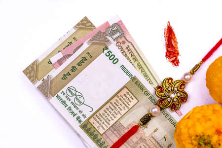 Raksha Bandhan - Elegant Rakhi and sweets with creative background of rice grains and kumkum, with Indian currency notes on white surface