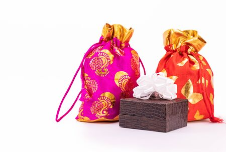 Potli bag or Dawstring bags and lather gift box decorated with white ribbon on white background
